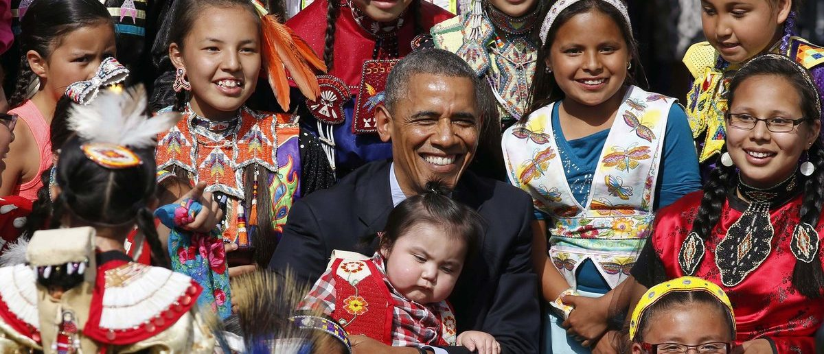 U.S. President Barack Obama holds a baby as he poses with children at the Cannon Ball Flag Day Celebration at the Cannon Ball Powwow Grounds on the Standing Rock Sioux Reservation in North Dakota, June 13, 2014. Obama on Friday made his first visit to an American Indian reservation since entering the White House on a trip to unveil new measures aimed at boosting education and economic opportunities for indigenous people. (REUTERS/Larry Downing)