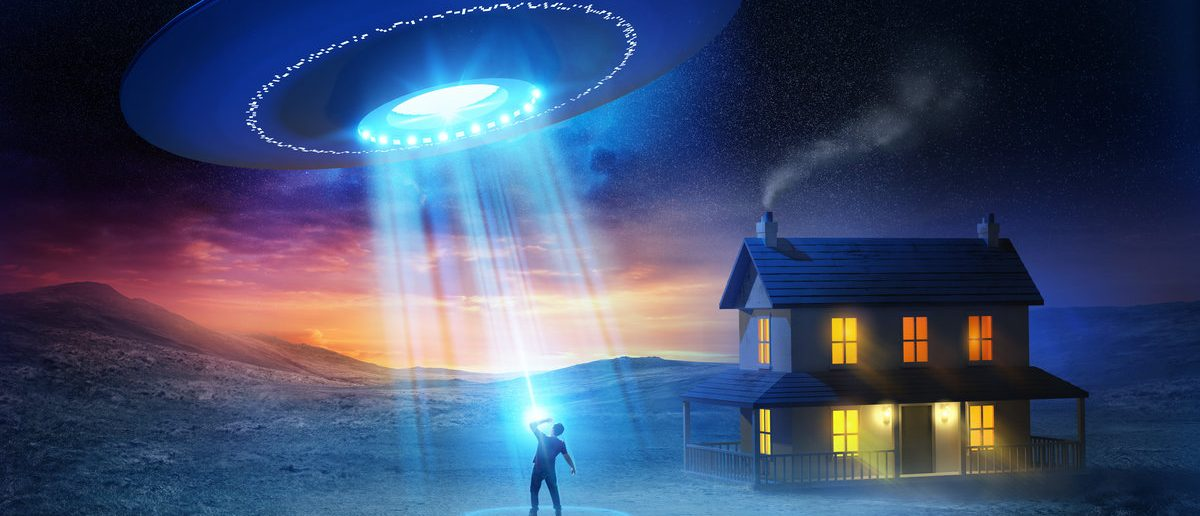A person being abducted by aliens in front of his house. (Shutterstock/solarseven)