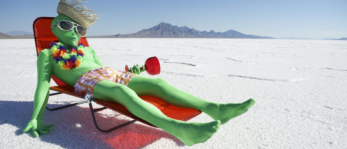 Green alien tourist goes on cheap holiday relaxing in beach chair with tropical drink (Shutterstock/lazyllama)
