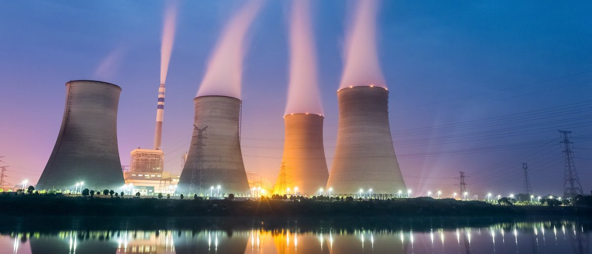 Nuclear reactors at night , cooling tower closeup with steam.(Shutterstock/chuyuss)
