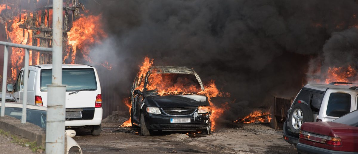 Huge fire of industrial buildings and cars. Open fire and black smoke. (Shutterstock/krivinis)
