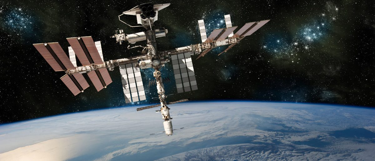 A depiction of the Space Shuttle docked at the International Space Station orbiting Earth. - Elements of this image furnished by NASA (Shutterstock/Marc Ward)
