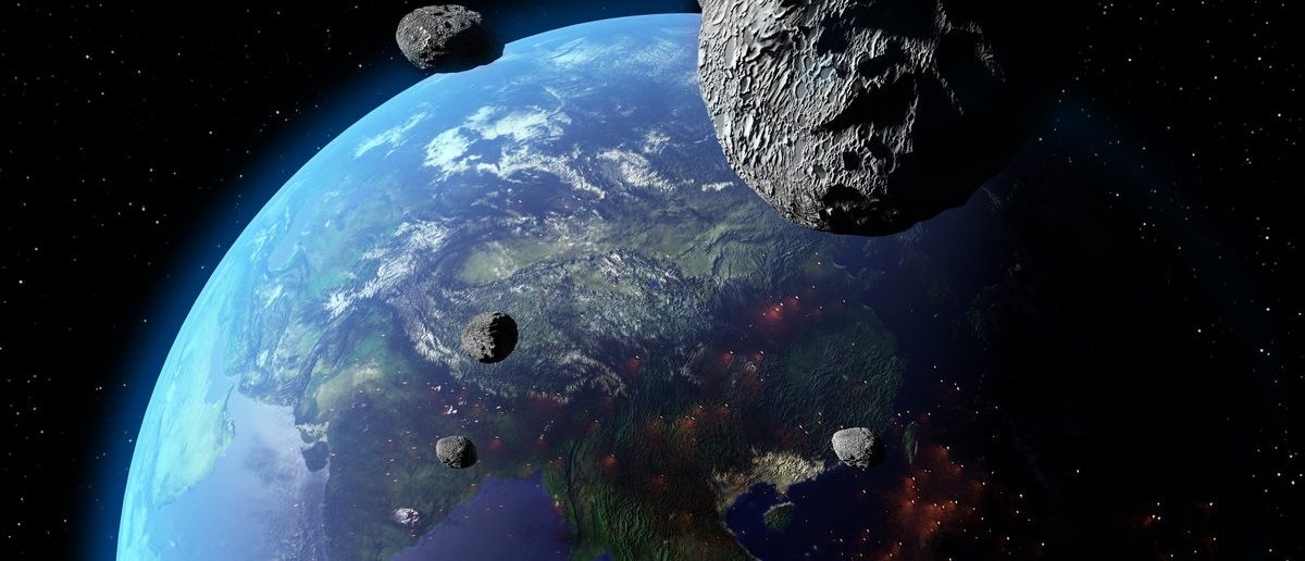 An illustration of asteroids approaching Earth. Earth land and clouds texture maps courtesy of NASA (Shutterstock/AuntSpray)