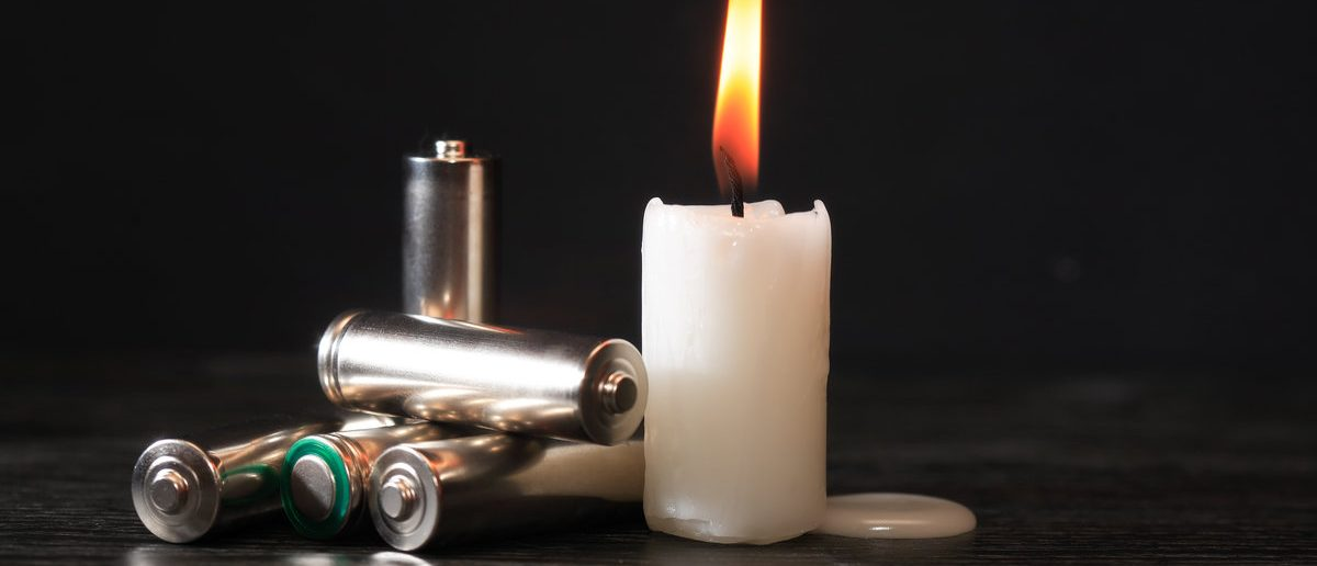 Blackout concept. Few batteries near lighting candle on dark background (Shutterstock/cosma)