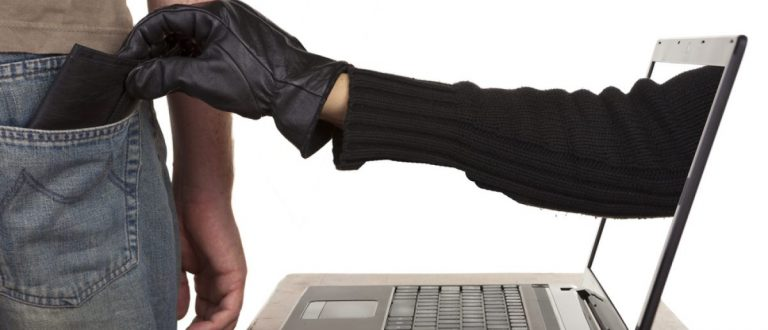 Internet theft - a gloved hand reaching through a laptop screen to steal a wallet. [Shutterstock - David Evison]