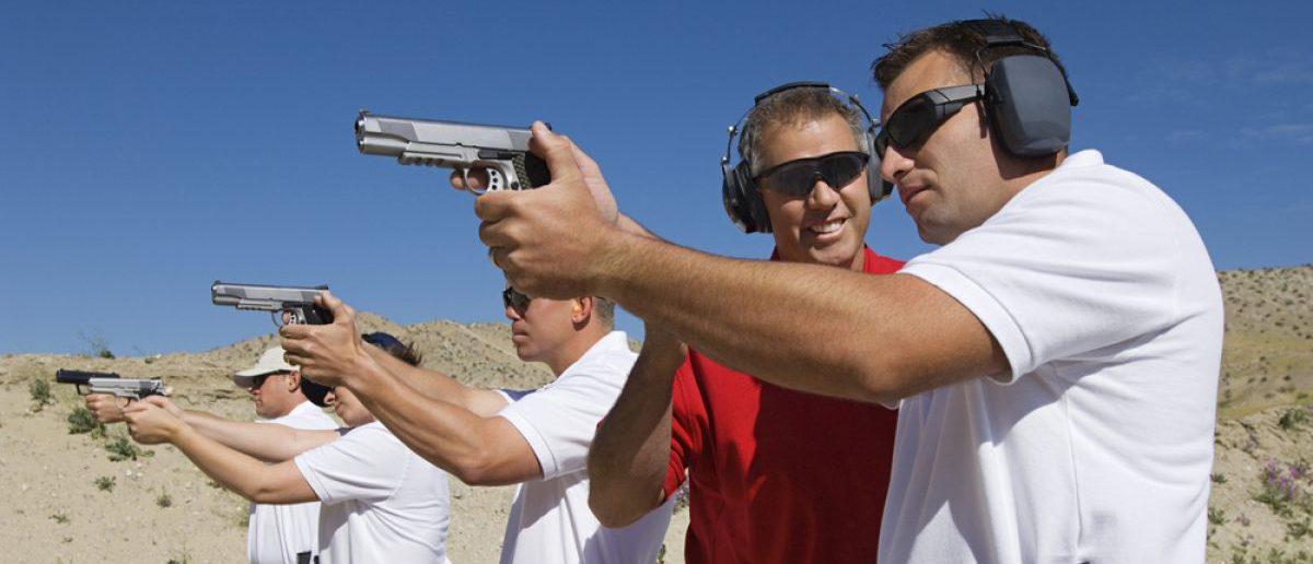 Lieutenant standing with troops holding guns on training. [Shutterstock - bikeriderlondon]