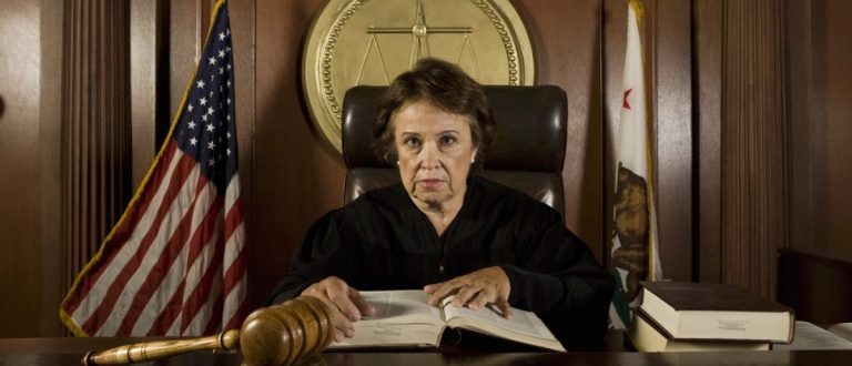 Portrait of a senior judge looking out into the courtroom. [Shutterstock - bikeriderlondon - 122182648]