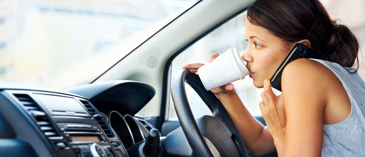 Businesswoman multitasking while driving, drinking coffee and talking on the phone. [Shutterstock - Daxiao Productions]