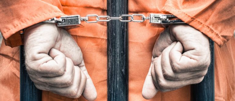 A handcuffed inmate behind prison bars.