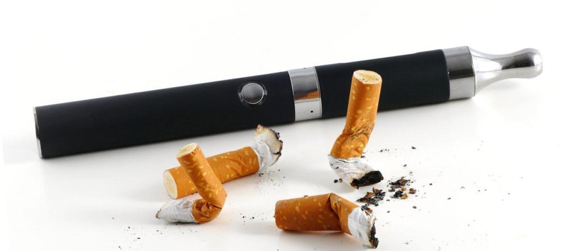An e-cigarette is shown next to cigarette butts. Shutterstock/Maren Winter