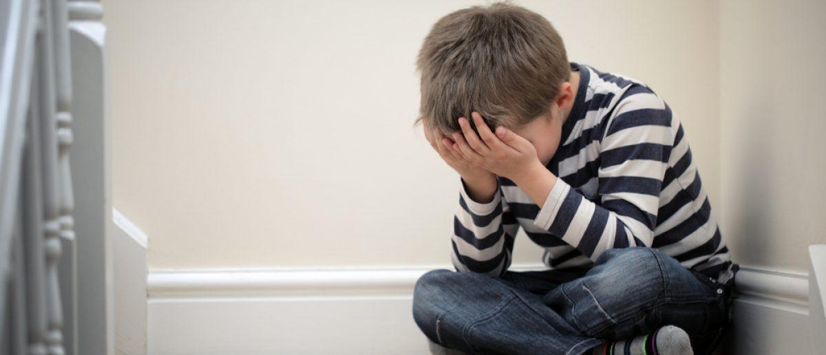 Upset child with head in hands sitting on staircase. [Shutterstock - Brian A Jackson]