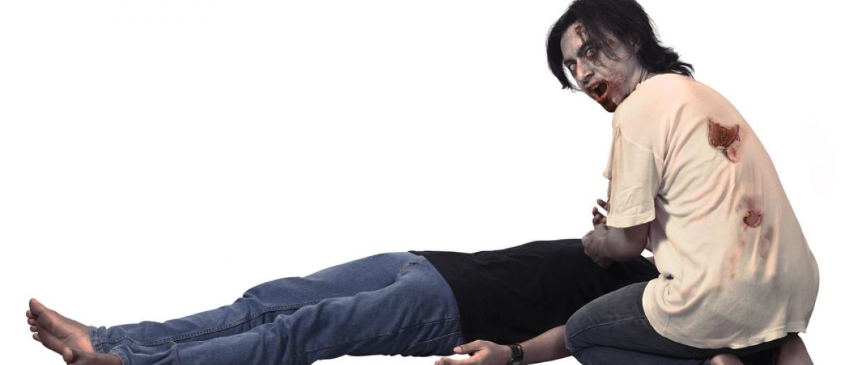 Scary male zombie eating corpse. [Shutterstock - leolintang]