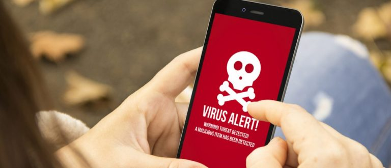 Cybersecurity: Woman holding a smartphone with virus alert on the screen. [Shutterstock - Georgejmclittle - 319423463]
