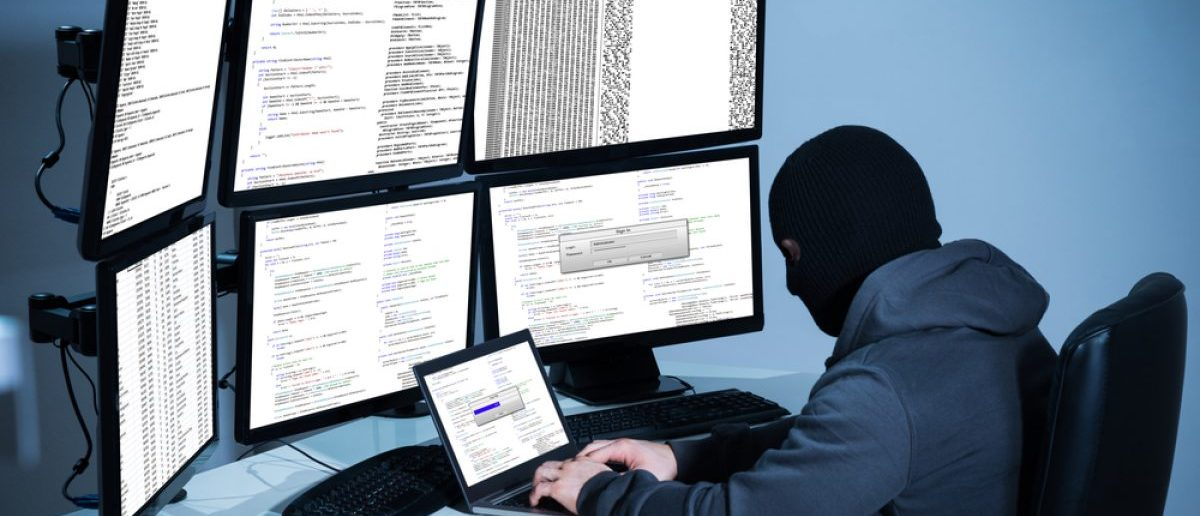 Hacker using laptop against multiple monitors at desk in office. [Shutterstock - Andrey_Popov - 360067064]