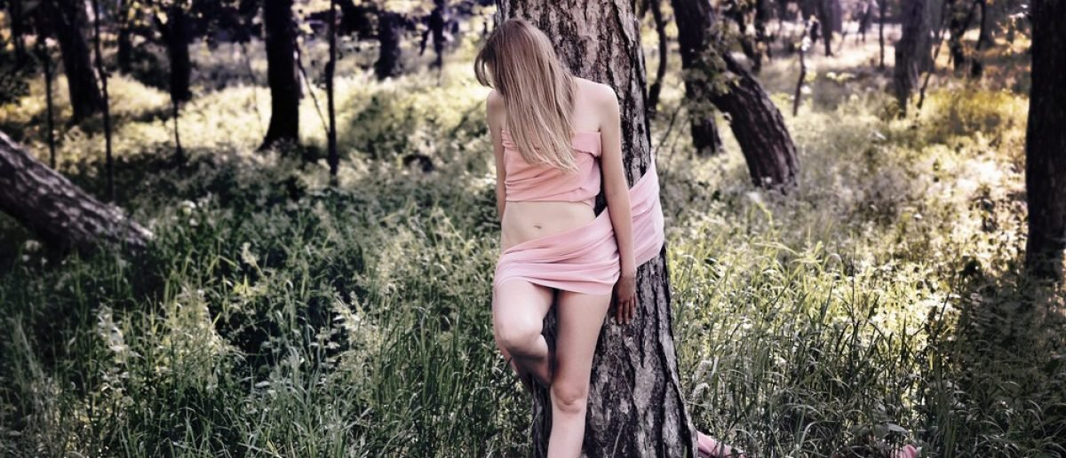 Lost in the forest. Naked woman tied with ribbon to a tree. [Shutterstock - andrey_l - 366831803]