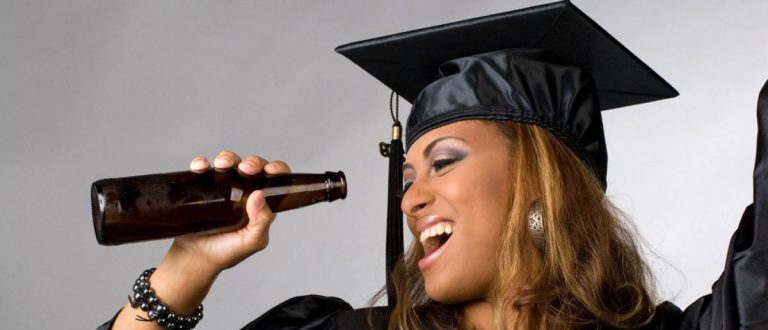A college graduate poses with a beer in her cap and gown. (Shutterstock/ARENA Creative)