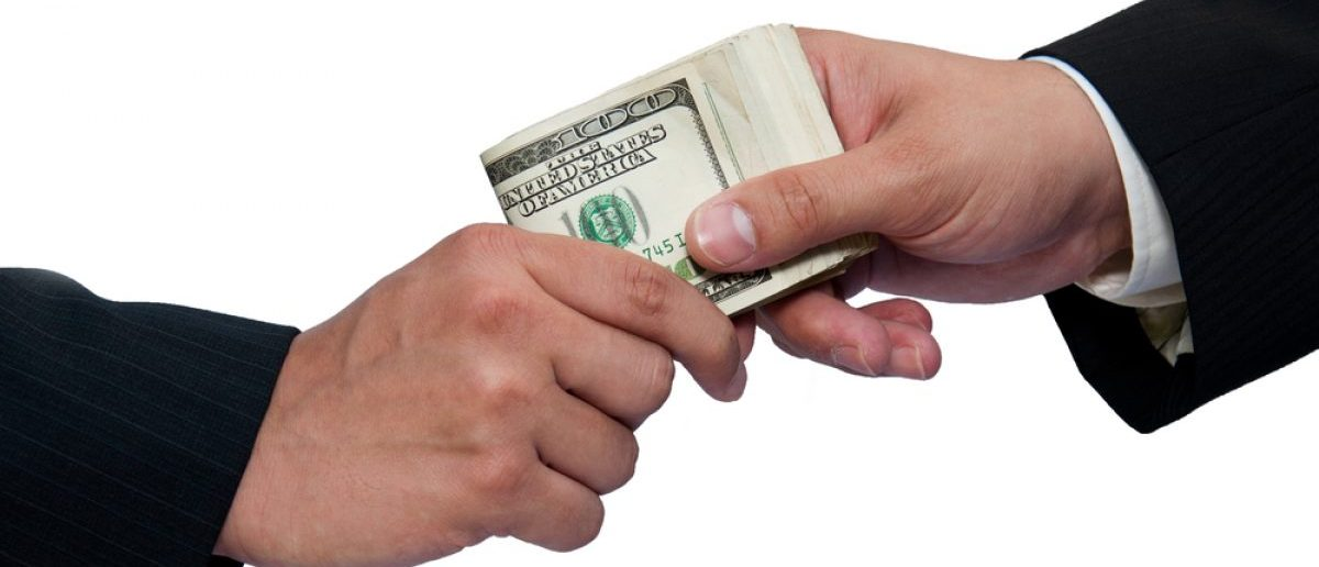 Two people agreeing to a bribe. [Shutterstock - Jan S.]