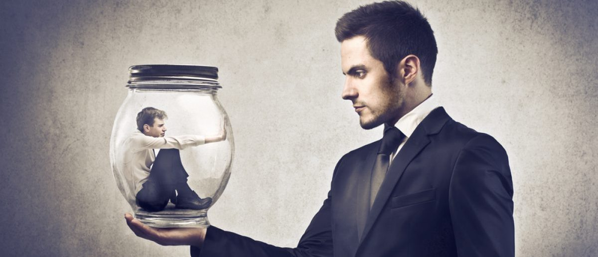 A boss holding a glass jar with a younger businessman trapped in it, exemplifying dominance. [Shutterstock - Ollyy - 99779465]
