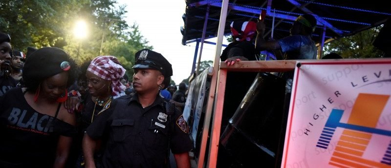 A New York City police officer guards a float participating in the overnight-into-dawn celebration called J'Ouvert in Brooklyn