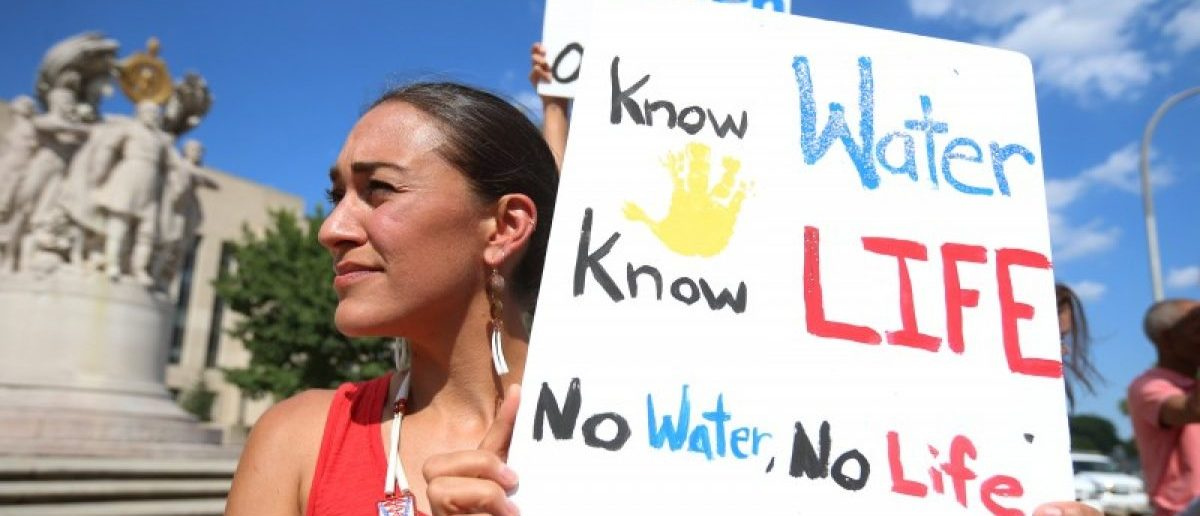 Heather Mendoza of Arlington, Virginia, holds up a sign as she protests outside the U.S. District Court in Washington, where a hearing was being held to decide whether to halt construction of an oil pipeline in parts of North Dakota where a Native American tribe says it has ancient burial and prayer sites, September 6, 2016. REUTERS/Kevin Lamarque