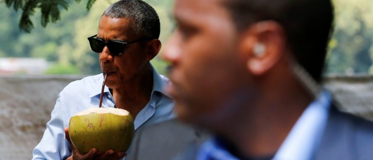 A Secret Service agent keeps watch as U.S. President Barack Obama drinks water of a fresh-cut coconut on a walk in Luang Prabang, Laos September 7, 2016. REUTERS/Jonathan Ernst
