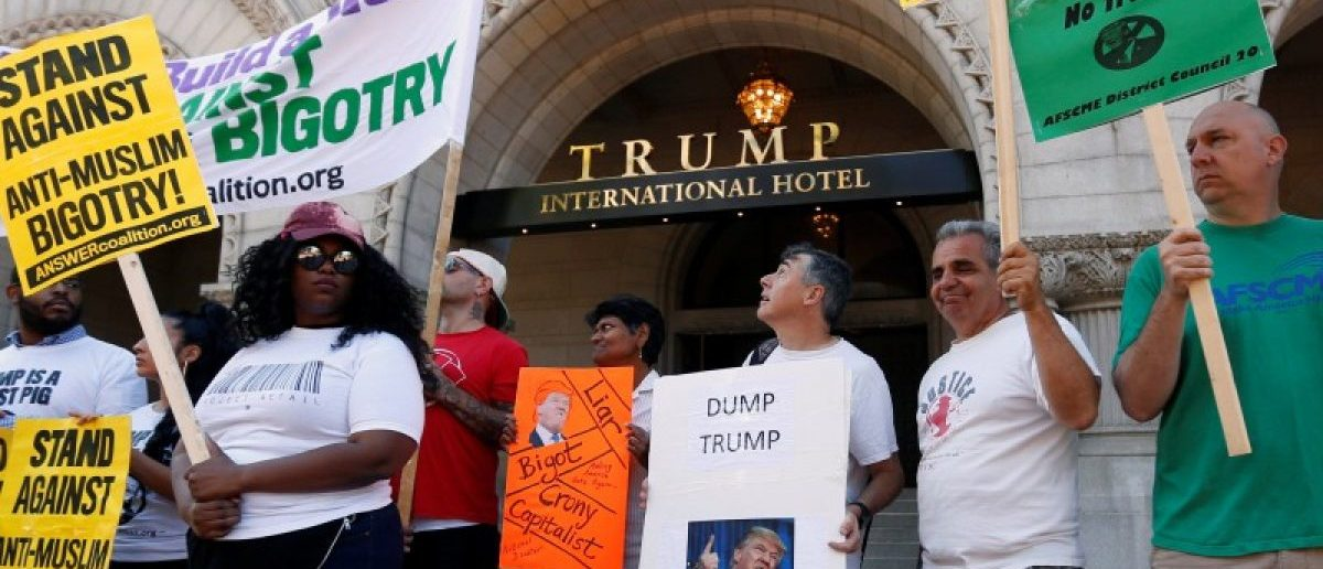 Protesters hold signs outside the new Trump International Hotel on it's opening day in Washington September 12, 2016. REUTERS/Kevin Lamarque