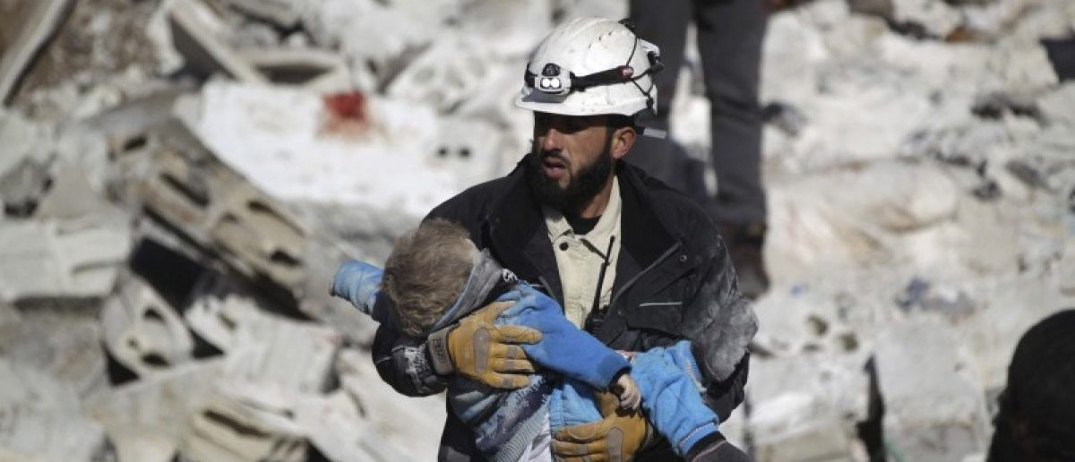 A civil defence member carries a dead child in a site hit by what activists said were airstrikes carried out by the Russian air force in the rebel-controlled area of Maaret al-Numan town in Idlib province, Syria. At least 70 people died in what activists said where four vacuum bombs dropped by the Russian air force, January 2016. REUTERS/Khalil Ashawi