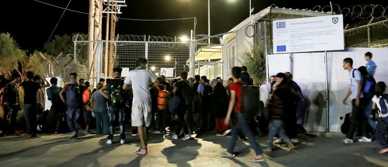 Refugees and migrants stand at the closed gate of the Moria migrant camp, after a fire at the facility, on the island of Lesbos, Greece, September 19, 2016. Intimenews/Manolis Lagoutaris/via REUTERS