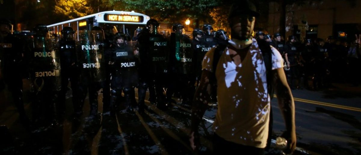 A demonstrator is seen near police in riot gear while continuing to protest after curfew in Charlotte, North Carolina, U.S., September 25, 2016. REUTERS/Mike Blake