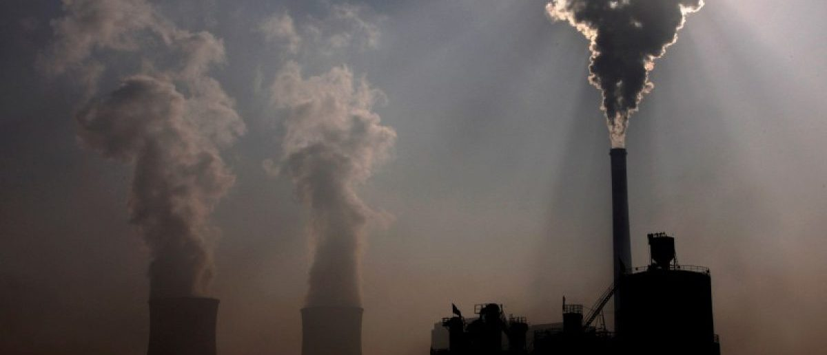 A coal-burning power plant can be seen behind a factory in the city of Baotou, in China's Inner Mongolia Autonomous Region October 31, 2010. REUTERS/David Gray/File Photo