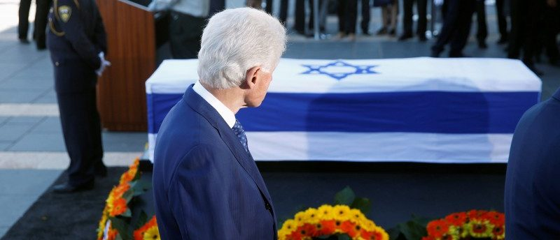 Former President Bill Clinton stands next to the flag-draped coffin of former Israeli President Shimon Peres, as he lies in state at the Knesset plaza, the Israeli parliament, in Jerusalem
