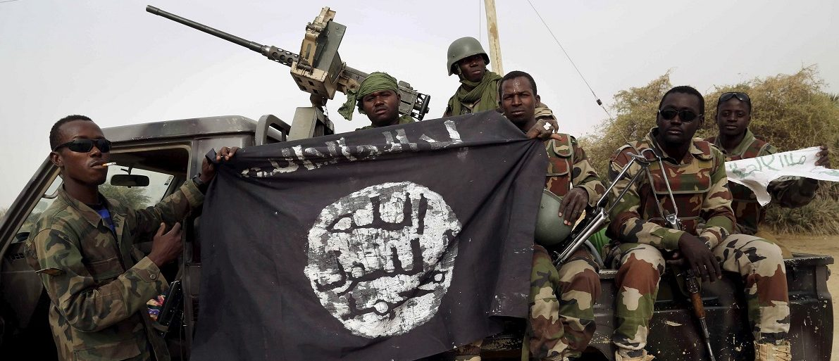 FILE PHOTO - Nigerian soldiers hold up a Boko Haram flag that they had seized in the recently retaken town of Damasak, Nigeria, March 18, 2015. REUTERS/Emmanuel Braun/File Photo