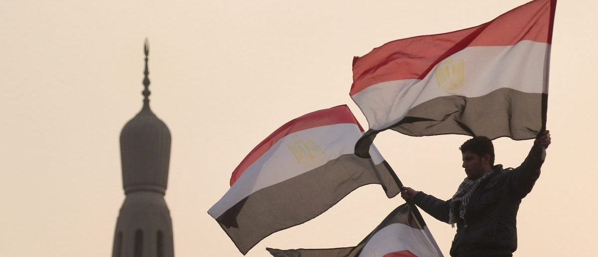 A youth waves Egyptian flags from a lamp post in Tahrir Square on February 1, 2011 in Cairo, Egypt. The Egyptian army has said it will not fire on protestors as they gather in large numbers in central Cairo. (Peter Macdiarmid/Getty Images)