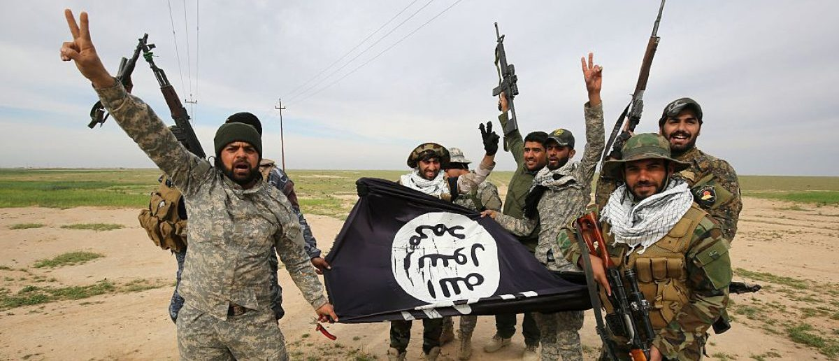 Iraqi Shiite fighters from the Popular Mobilisation units pose with a Islamic State (IS) group flag on March 3, 2016. (AHMAD AL-RUBAYE/AFP/Getty Images)
