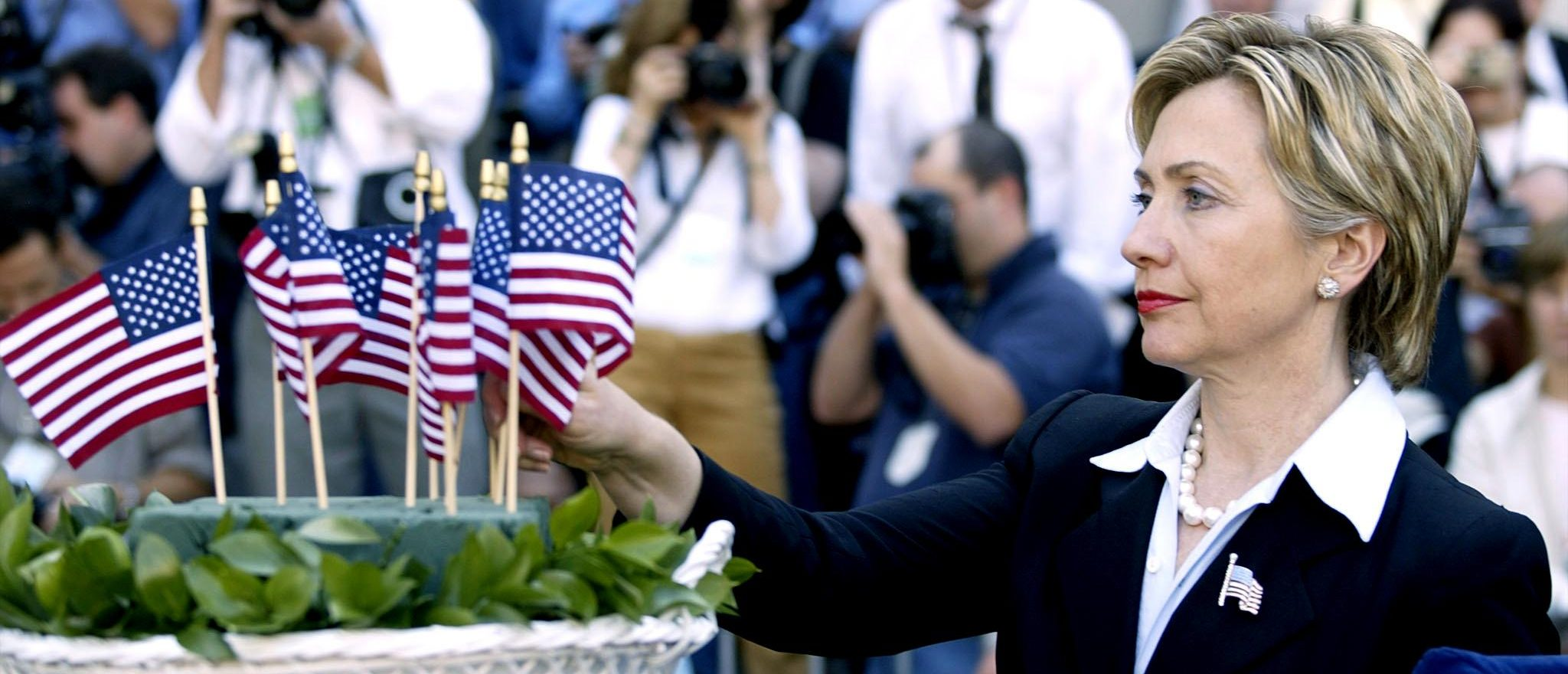 Hillary Clinton places a flag during a ceremony at Ground Zero of the World Trade Center site during a ceremony in New York, 06 September 2002. (Getty Images)