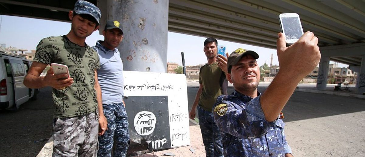 Iraqi government forces take pictures with their phones as they secure an area in western Fallujah, 50 kilometers (30 miles) from the Iraqi capital Baghdad, after Iraqi forces retook the embattled city from the Islamic State group on June 27, 2016. [HAIDAR MOHAMMED ALI/AFP/Getty Images]