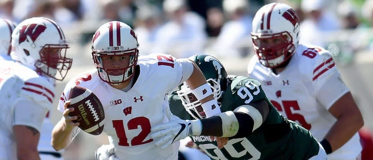 EAST LANSING, MI - SEPTEMBER 24: Alex Hornibrook #12 of the Wisconsin Badgers is grabbed by Raequan Williams #99 of the Michigan State Spartans as he runs downfield during the game at Spartan Stadium on September 24, 2016 in East Lansing, Michigan. (Photo by Bobby Ellis/Getty Images)