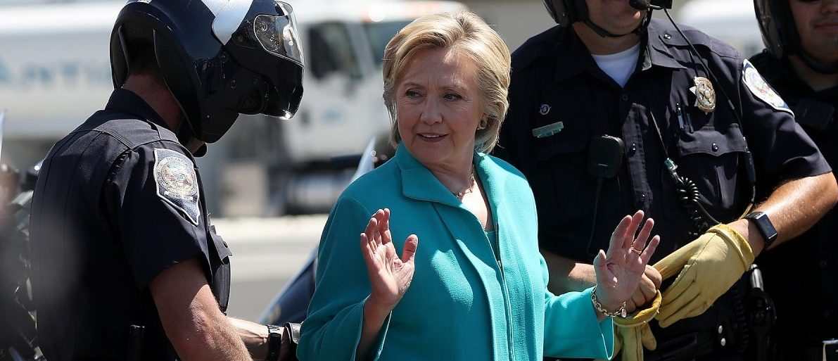RENO, NV - AUGUST 25:  Democratic presidential nominee former Secretary of State Hillary Clinton talks with Reno police officers before getting onto her  plane at Reno Tahoe International Airport on August 25, 2016 in Reno, Nevada. Hillary Clinton delivered a speech about republican presidential nominee Donald Trump's policies.  (Photo by Justin Sullivan/Getty Images)