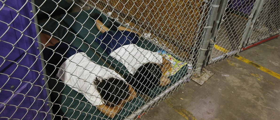 Two female detainees sleep in a holding cell as the children are separated by age group and gender at the U.S. Customs and Border Protection Nogales Placement Center in Nogales Arizona