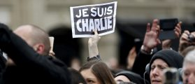 Person holds up a sign during a ceremony at Place de la Republique square to pay tribute to the victims of last year's shooting at the French satirical newspaper Charlie Hebdo, in Paris