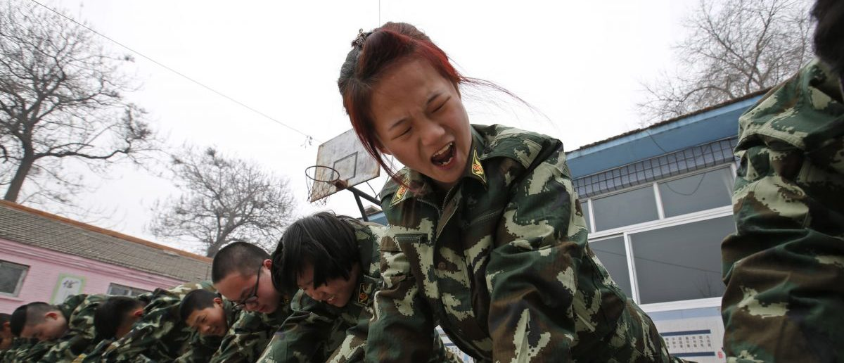 Students receive a group punishment during a military-style close-order drill class at the Qide Education Center in Beijing February 19, 2014. The Qide Education Center is a military-style boot camp which offers treatment for internet addiction. As growing numbers of young people in China immerse themselves in the cyber world, spending hours playing games online, worried parents are increasingly turning to boot camps to crush addiction. Military-style boot camps, designed to wean young people off their addiction to the internet, number as many as 250 in China alone. Picture taken February 19, 2014. REUTERS/Kim Kyung-Hoon