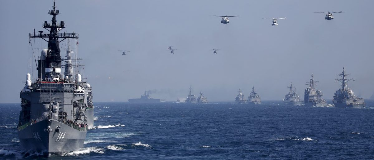 Japan's Maritime Self-Defense Force (JMSDF) destroyer Kurama (L), which is carrying Japan's Prime Minister Shinzo Abe, leads the JMSDF fleet and helicopters during its fleet review at Sagami Bay, off Yokosuka, south of Tokyo, October 18, 2015. REUTERS/Toru Hanai