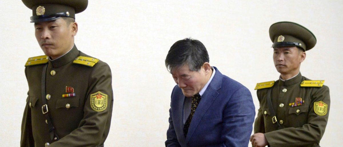 A man (C) who identified himself as Kim Dong Chul, previously said he was a naturalised American citizen and was arrested in North Korea in October, leaves after a news conference in Pyongyang, North Korea, in this photo released by Kyodo March 25, 2016. The Korean-American man who had been detained in North Korea has confessed to trying to steal military secrets from the isolated state, Japan's Kyodo and China's Xinhua news agencies reported on Friday. Mandatory credit REUTERS/Kyodo