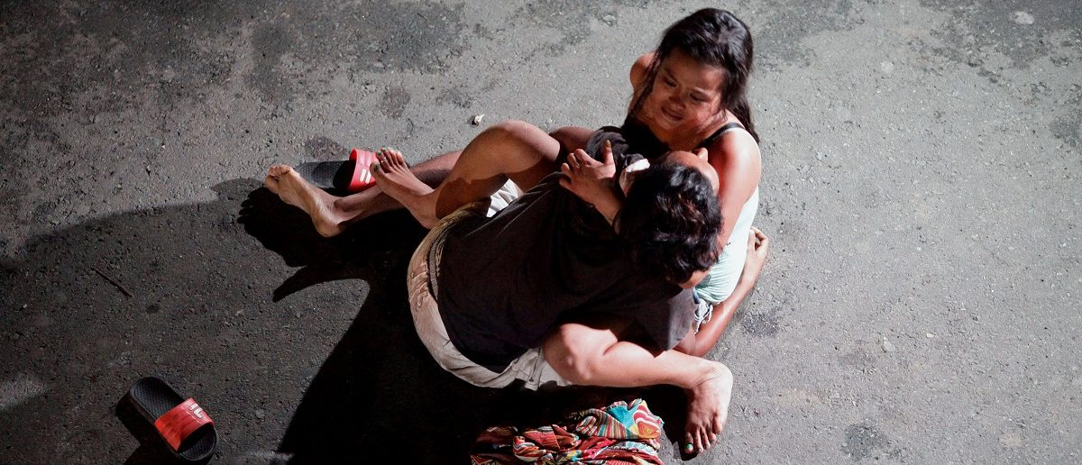 """Jennelyn Olaires, 26, cradles the body of her partner, who was killed on a street by a vigilante group, according to police, in a spate of drug related killings in Pasay city, Metro Manila, Philippines July 23, 2016. A sign on a cardboard found near the body reads: """"Pusher Ako"""", which translates to """"I am a drug pusher."""" REUTERS/Czar Dancel"""