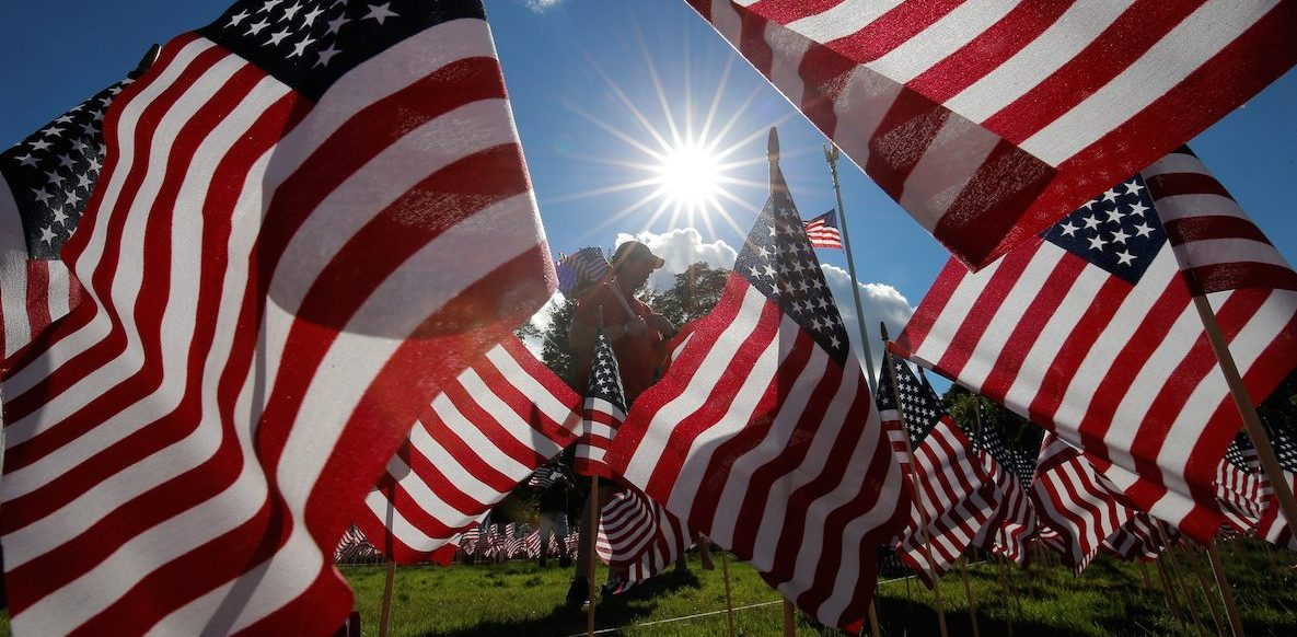 A man takes part in planting some of the 3,000 flags placed in memory of the lives lost in the September 11, 2001 attacks, at a park in Winnetka REUTERS/Jim Young