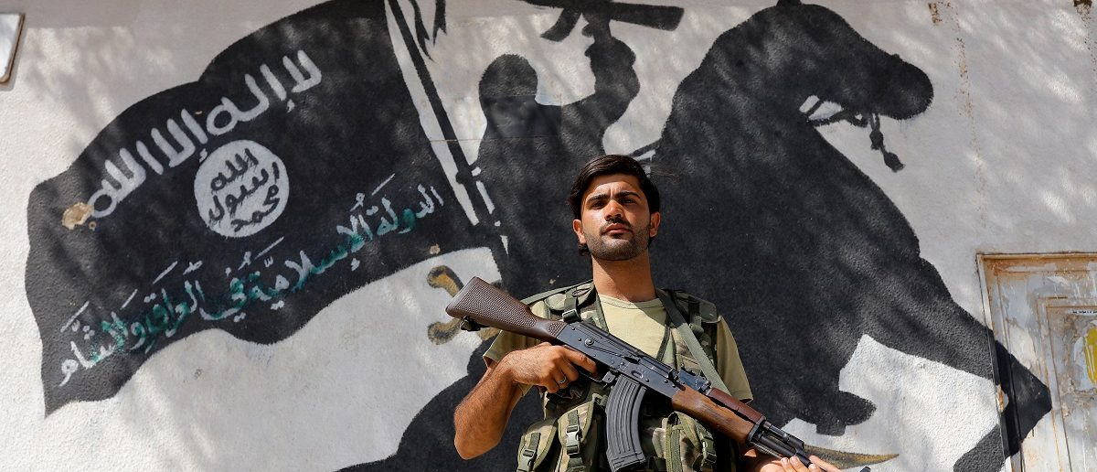 A member of Turkish-backed Free Syrian Army (FSA), seen with a mural of the Islamic State in the background, stands guard in front of a building in the border town of Jarablus, Syria, August 31, 2016. REUTERS/Umit Bektas