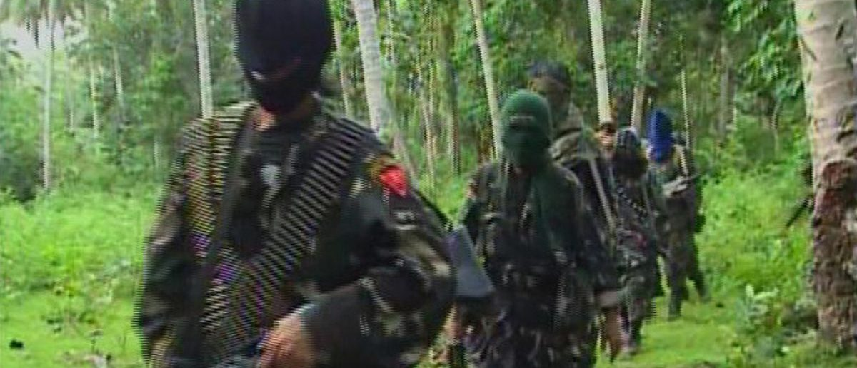Abu Sayyaf rebels are seen in the Philippines in this video grab made available February 6, 2009. Three aid workers, including two Europeans, kidnapped nearly four weeks ago on a remote Philippine island appeared in good condition in video footage broadcast by local television on Friday. The International Committee of the Red Cross (ICRC) workers, kidnapped by Abu Sayyaf rebels, were shown talking to an unidentified man while standing in a forested area, believed to be in the interior of southern Jolo island. REUTERS/Philippine National Red Cross via Reuters TV