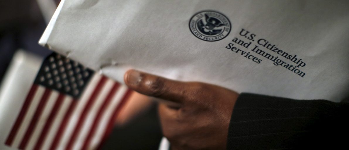 A man holds an envelope from the U.S. Citizenship and Immigrations Service during a naturalization ceremony at the National Archives Museum in Washington