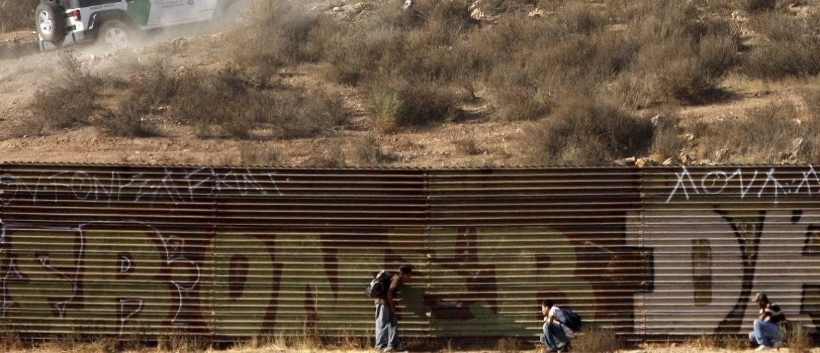 Immigrants hide from a border patrol vehicle while waiting a chance to cross into the United States at the border fence on the outskirts of the Tijuana September 19, 2009. Mexico's violent drug gangs are increasingly kidnapping illegal migrants for ransom and forcing them to carry narcotics into the United States as they muscle into the lucrative trade of smuggling people across the border. Picture taken September 19, 2009. REUTERS/Jorge Duenes