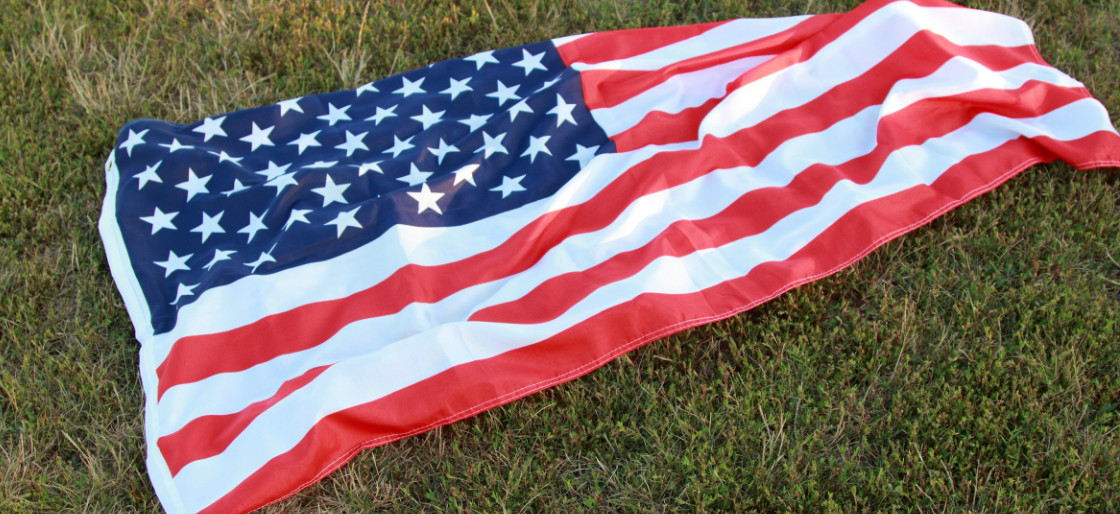 US flag on the grass Shutterstock/Maryna Kulchytska